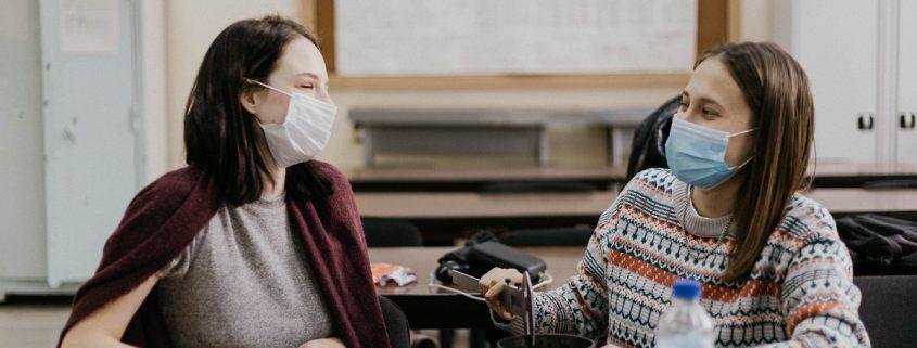 Two teachers wearing masks talking in a classroom