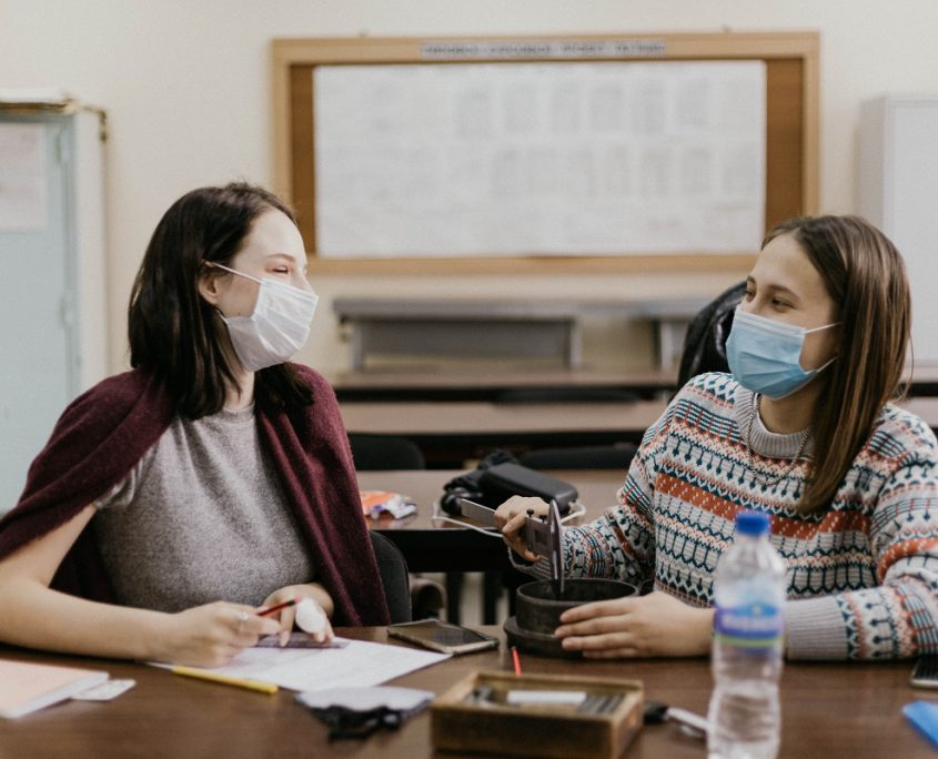 Two teachers wearing masks talking in a classroom