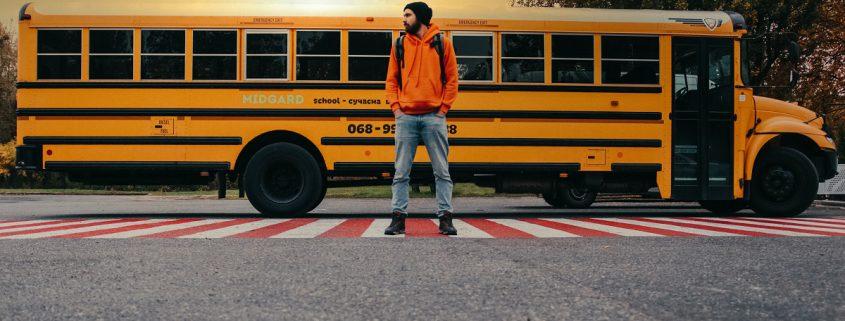 High School Student Standing in front of a school bus